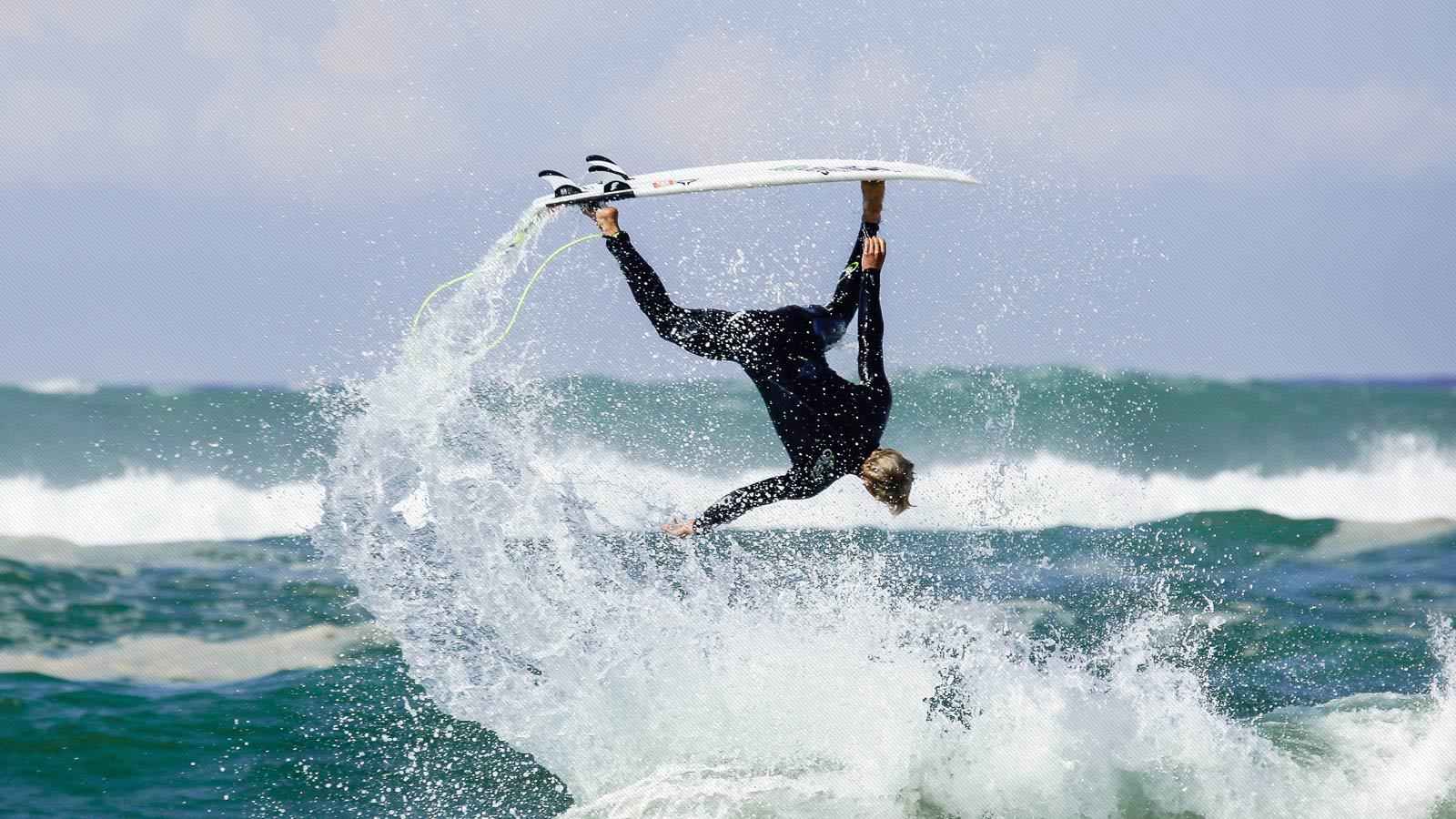 surfista profesional John John Florence volando y en posicion totalmente del revés por encima de una ola
